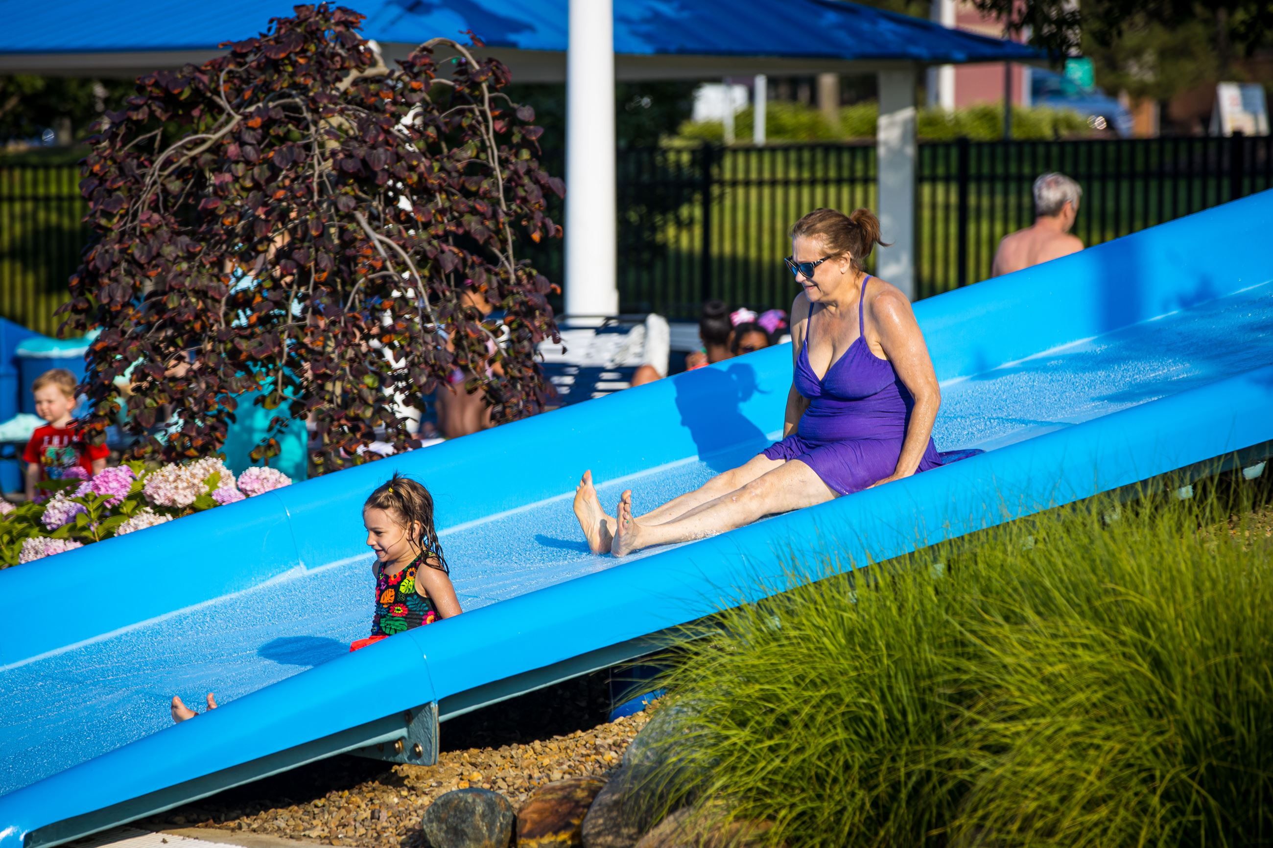 A child and woman use the slide at the Beachwood Family Aquatic Center