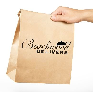 Hand holding a paper bag that says Beachwood Delivers