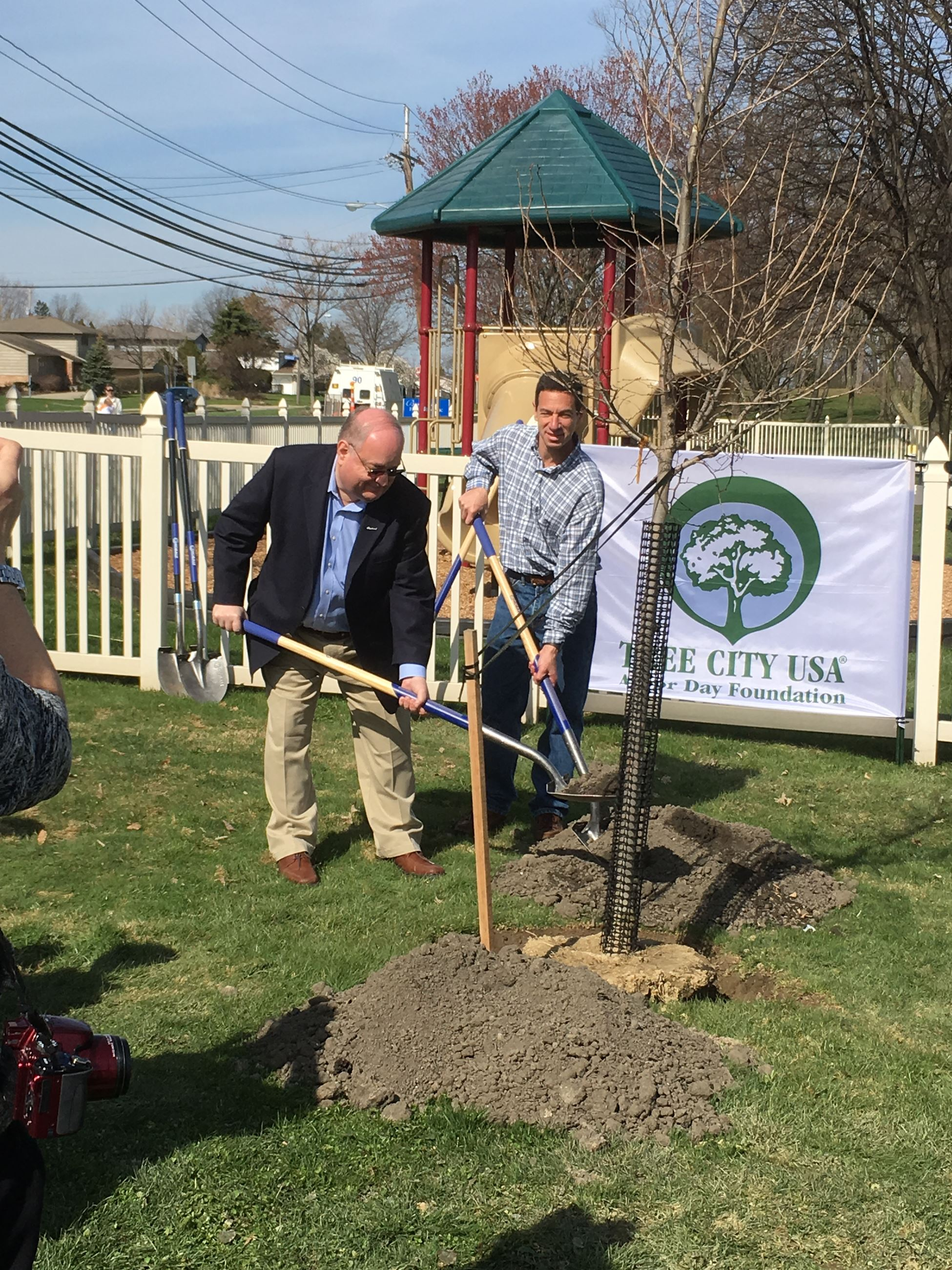 Mayor Horwitz and Councilman Justin Berns are shoveling dirt around a newly planted tree for Arbor D