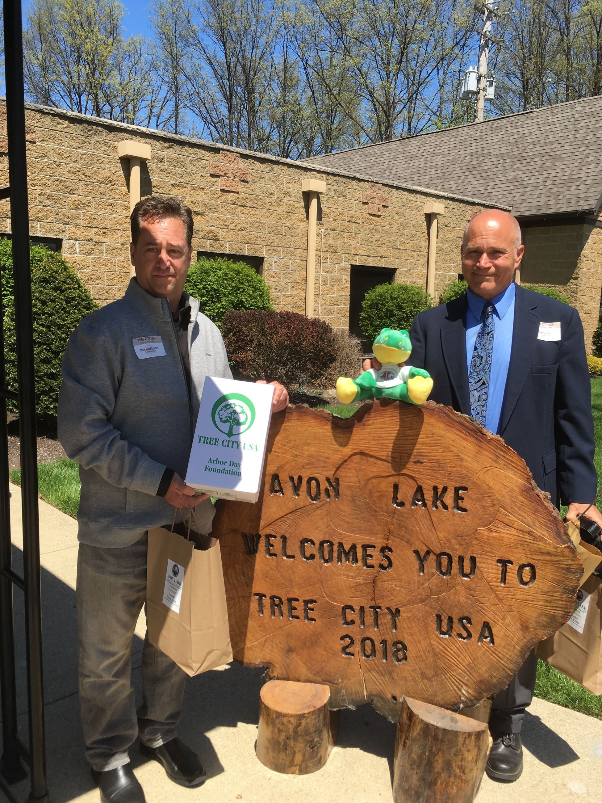 Dan Burkholder and Chris Vild are holding the 2018 Tree City USA award and a plush stuffed alligator