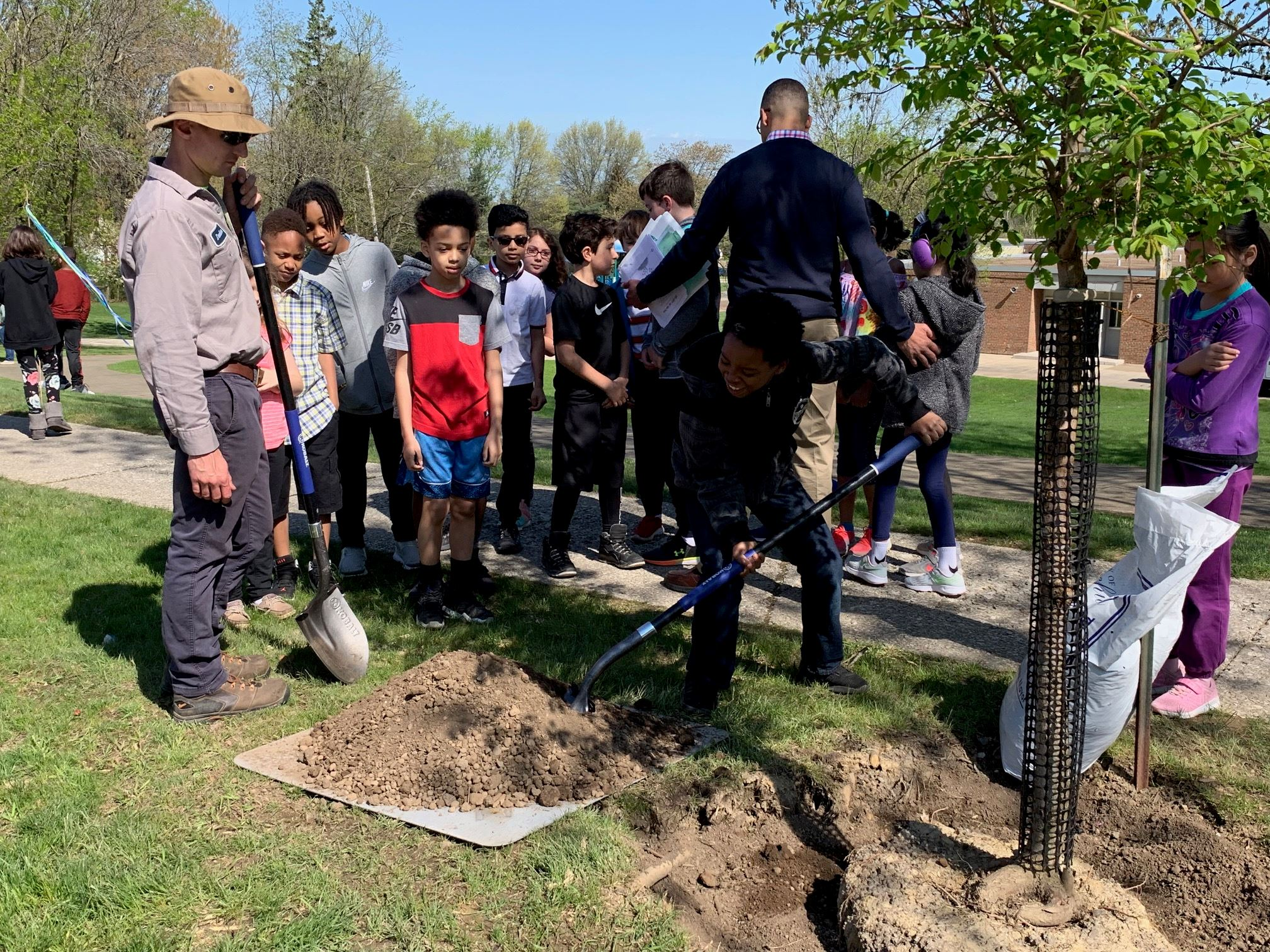 Students from Hilltop School plant a tree with assistance from the Beachwood Public Works Department