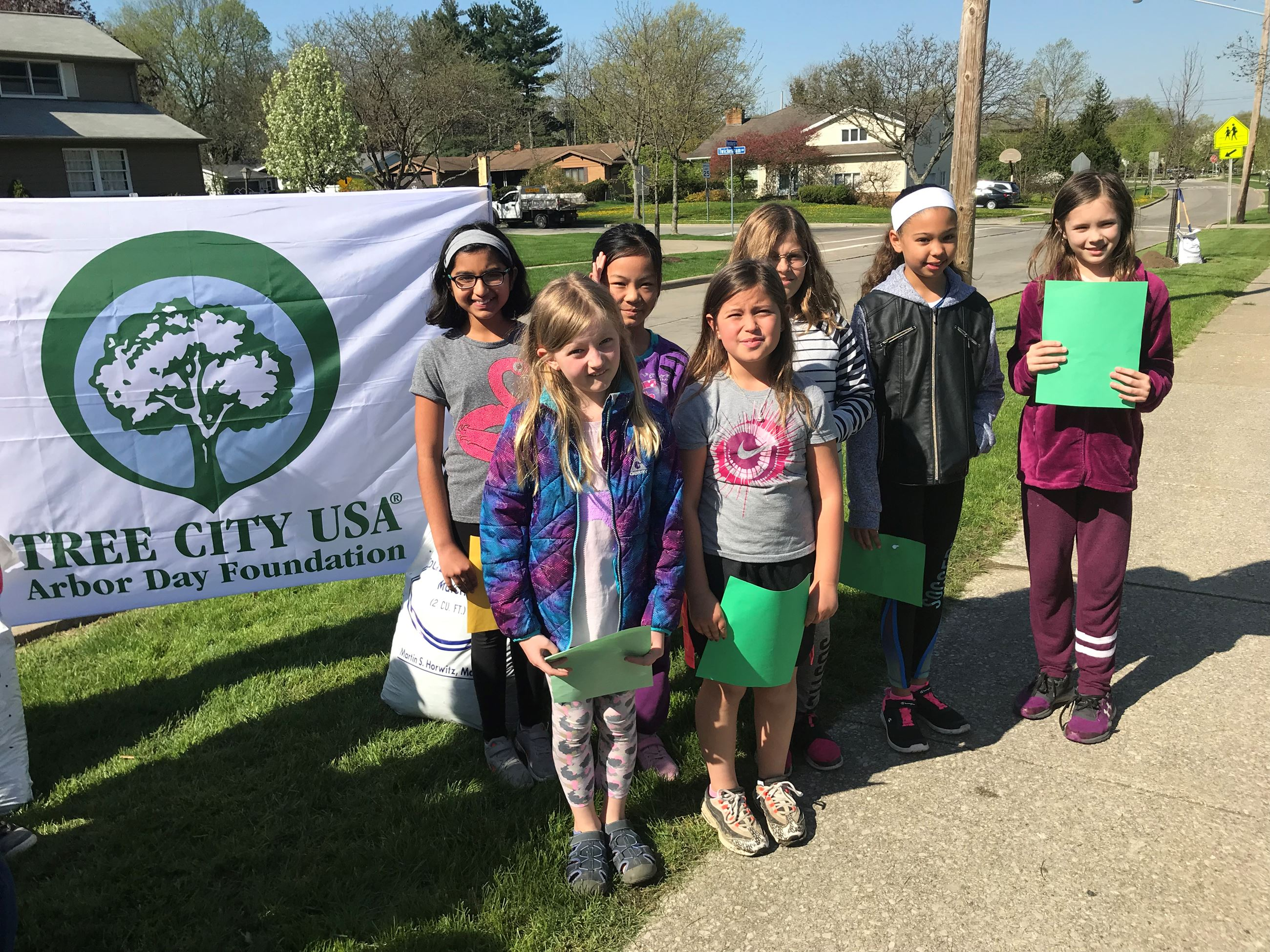 Hilltop students, poems in hand, wait to read them in front of Arbor Day banner.