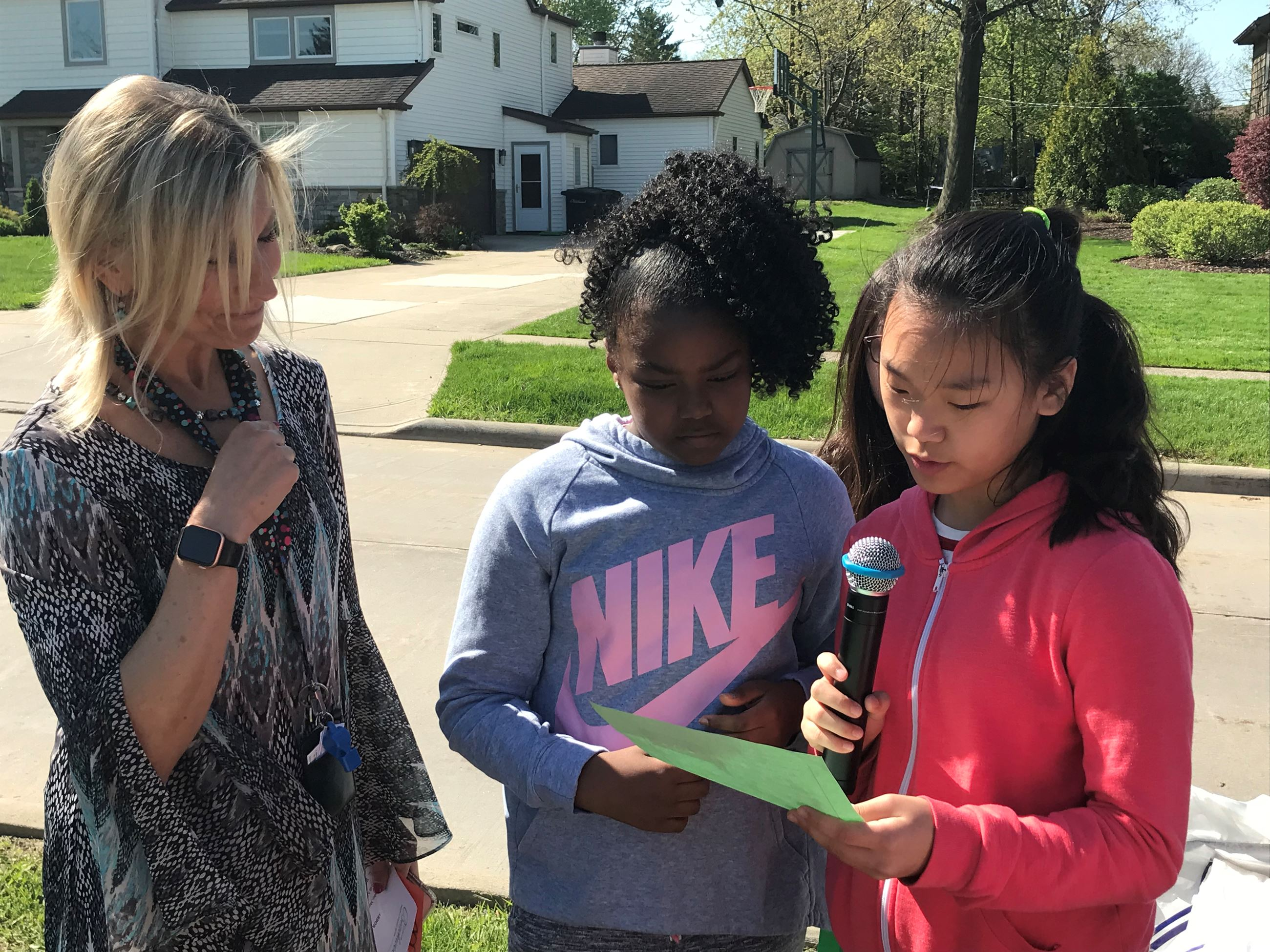 Two Hilltop students read an Arbor Day poem while Alesha Trudell, fourth grade teacher looks on.
